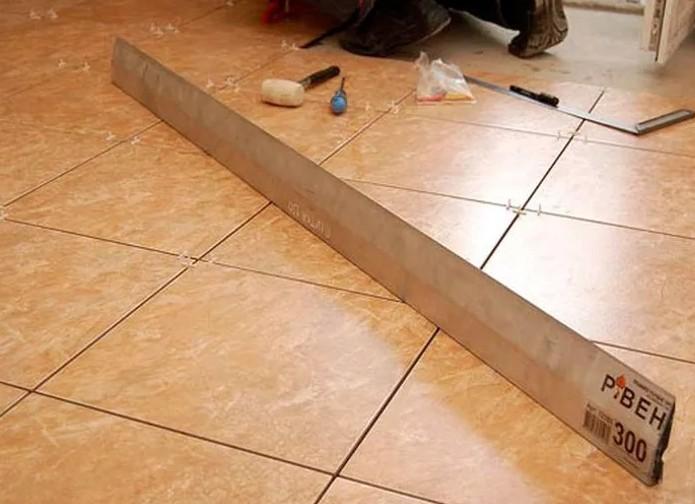 Проверка плитки длинным уровнем